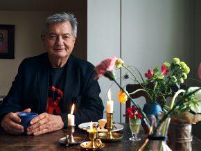 Erik Erichsen, rebellkirurgen sitter vid sitt matbord. Blommor och ljus står på bordet.
